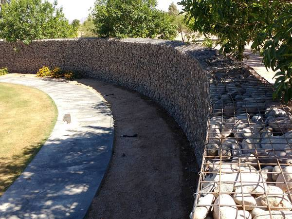 Welded gabion walls are installed beside of footpath in the park.