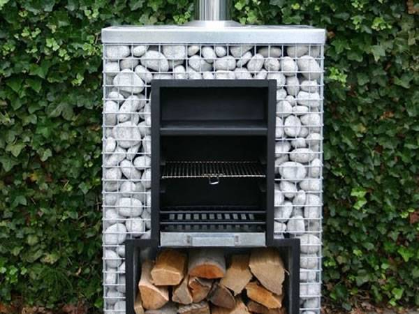 A gabion BBQ with a chimney on the top, a BBQ plate on the wood and some wood at the bottom.