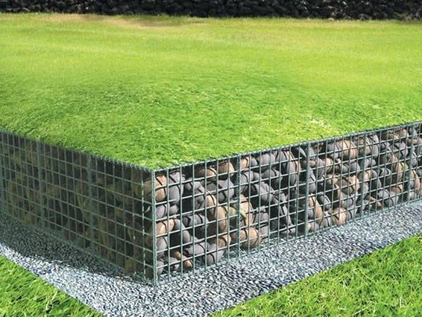 Gabion basket is filled with pebbles with a layer of grass on it.