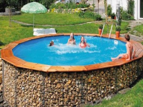 A round gabion swimming pool with 3 people swimming in it and one sitting on it.