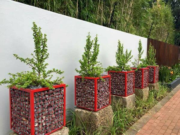 Red color gabion planters with angel steel beside of the garden wall.