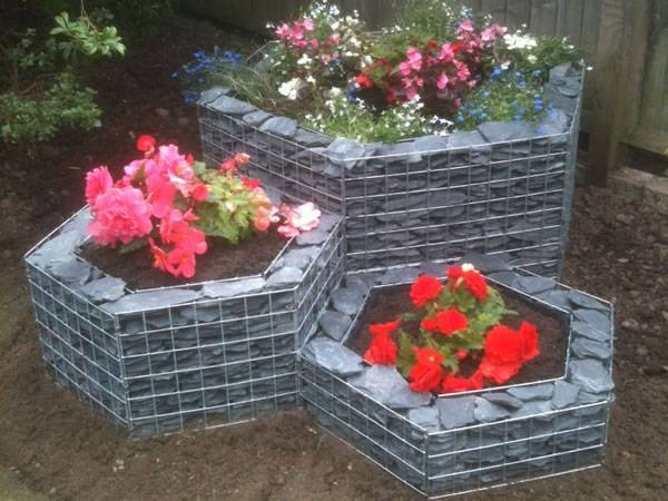#Three hexagonal shape gabion planters with flowers in it.