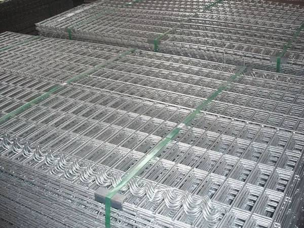 Several bundles of welded wire mesh panels and spiral binders on the ground.