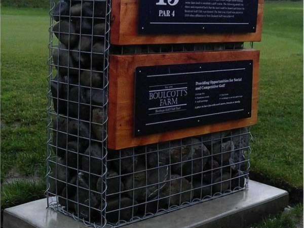 A gabion basket is filled with rocks with two boards on as a sign.