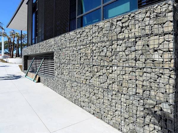 A line of welded gabions are installed beside of a office building.