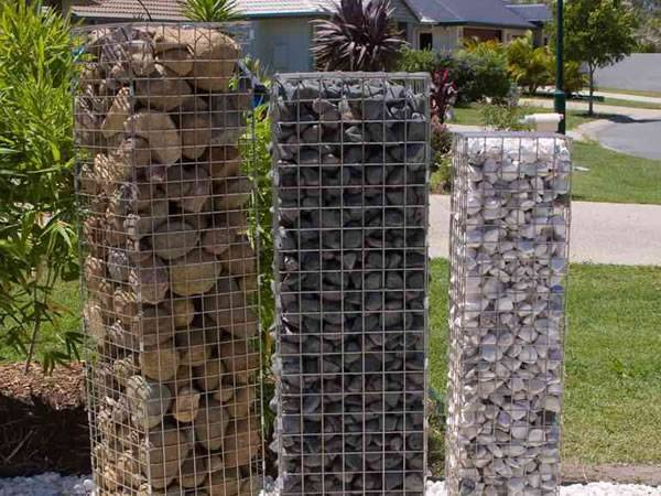 Three gabion posts is filled with different materials on pebble ground.