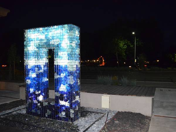A gabion basket is filled with colored rocks and with LED shining in the dusk.