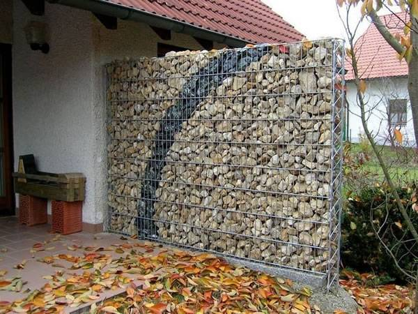 A gabion retaining wall is filled with rocks as retaining wall in a yard.